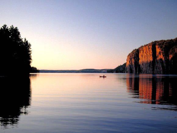 Un bateau sur le lac à côté d'un gros rocher