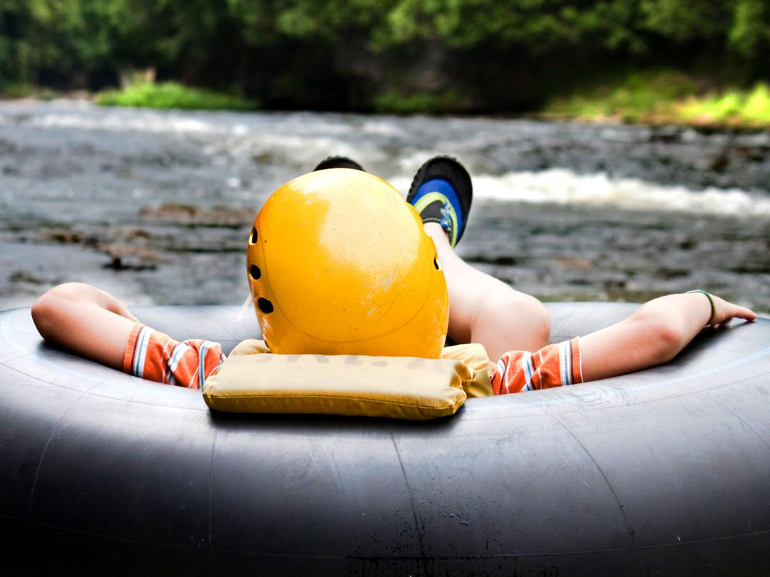 A young boy floats down a river in an inner tube