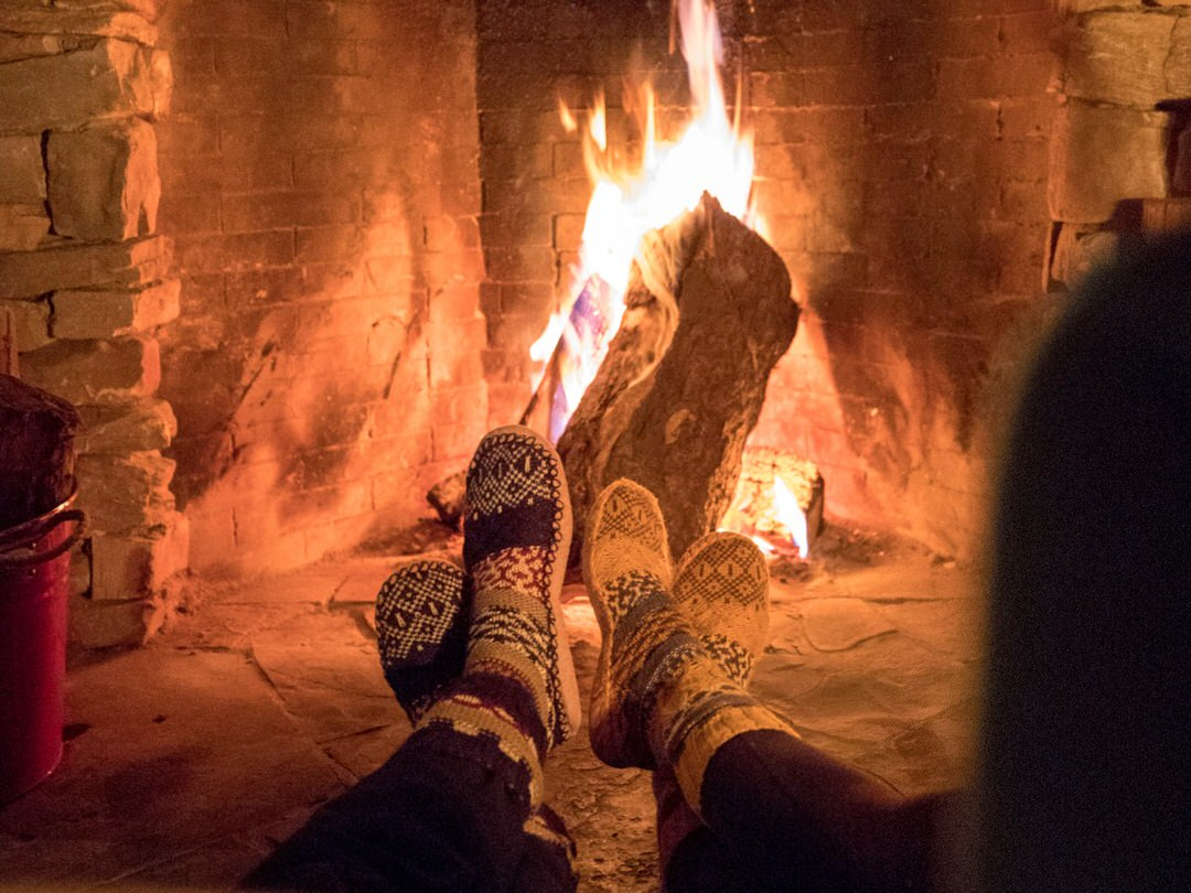Close up of two pairs of feet in socks in front of a fire place