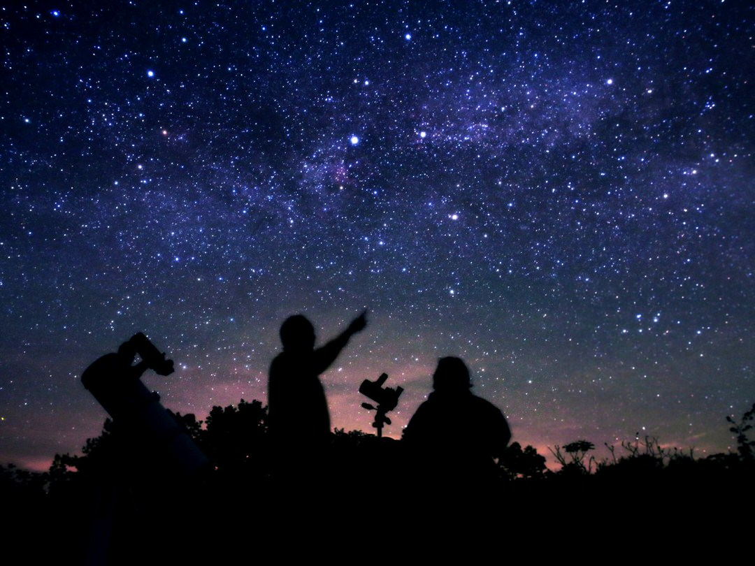 Silhouette of two people pointing and looking up at the stars