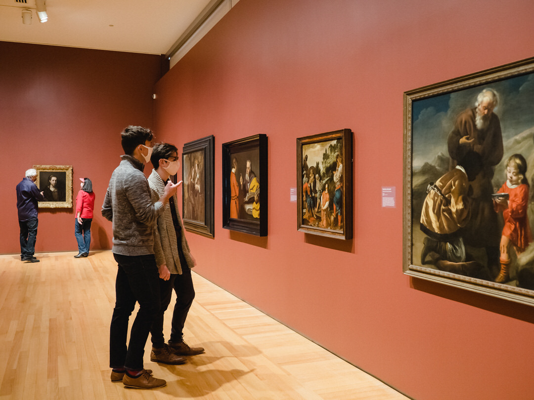 Groups of viewers commenting animatedly in front of paintings