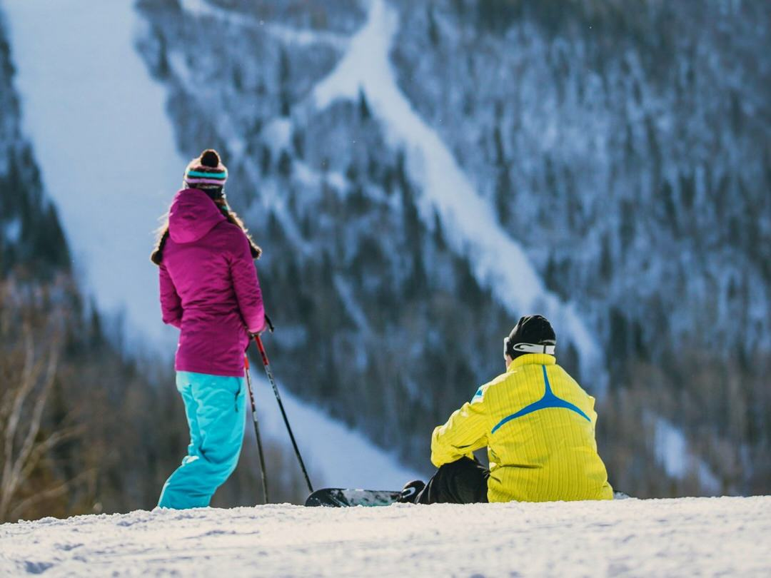 A couple pause to take in the scenic view on a ski hill