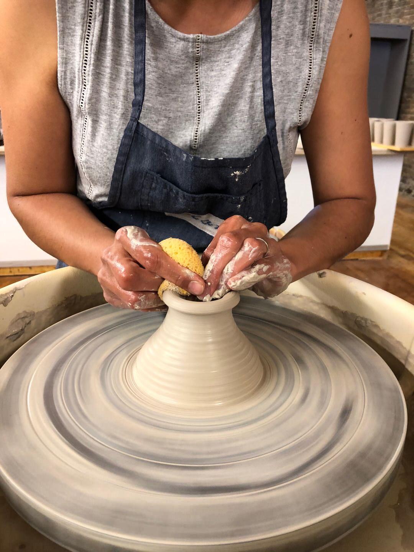 Close-up of a woman sculpting a vase at a sculpting table