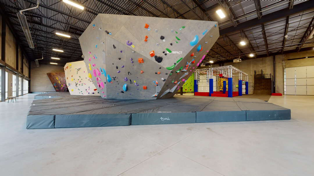 Grey rock climbing wall with colourful handles