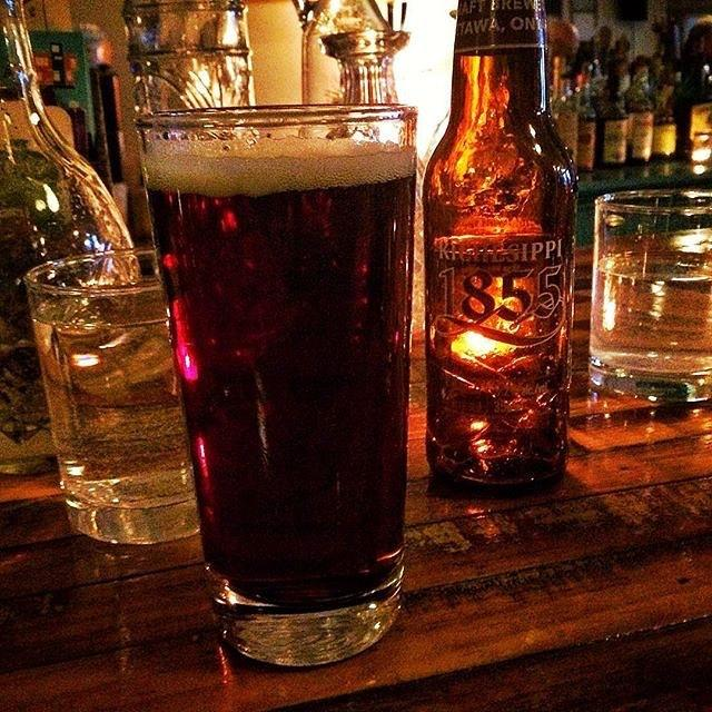Close up of a glass of a dark ale beside a bottle of beer sitting a top a bar