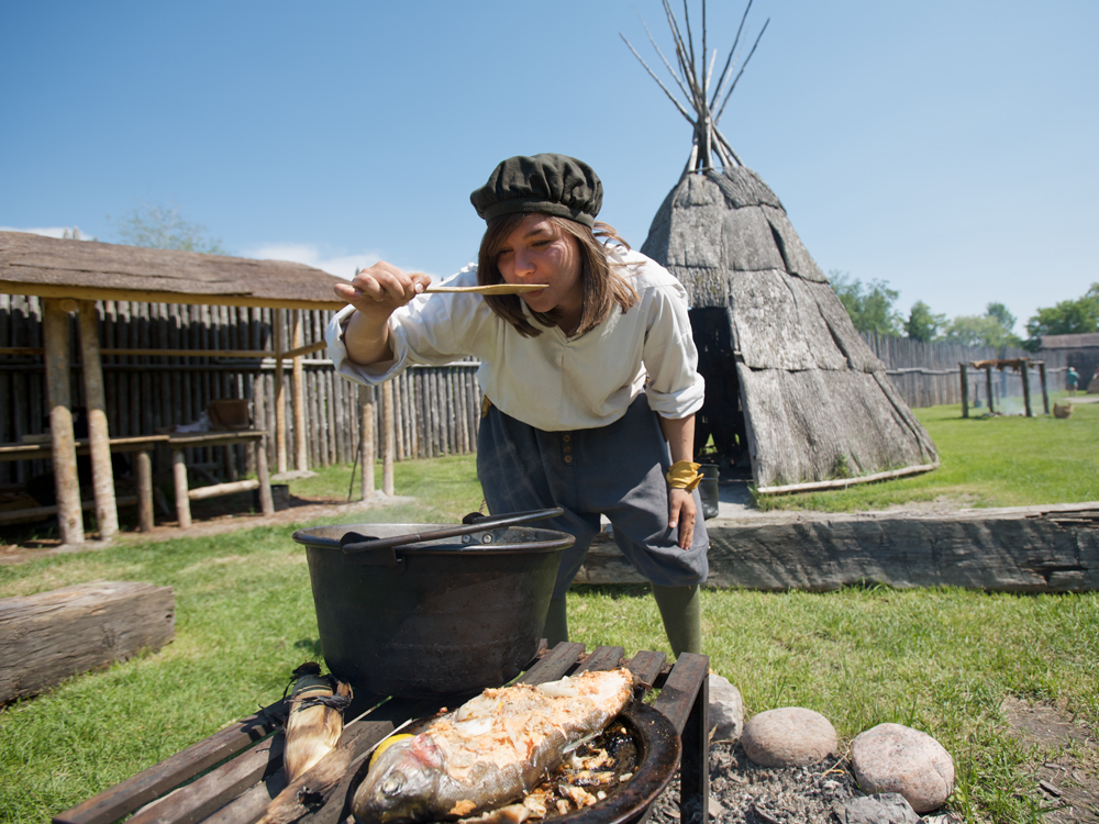 A person in costume cooks over an open fire