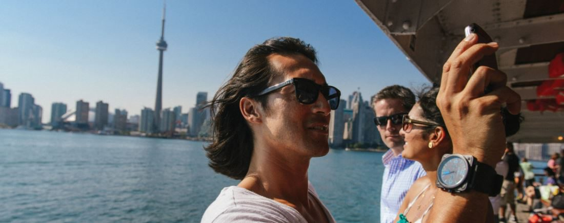 A man takes a selfie on a boat cruise overlooking the Toronto.
