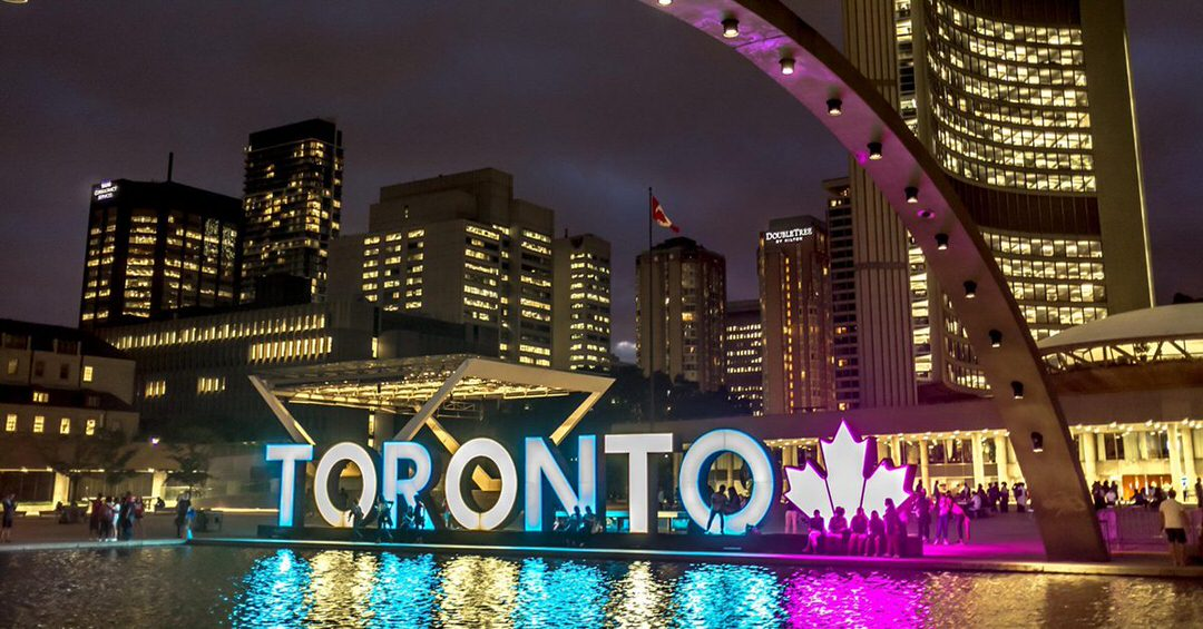 People enjoying the evening in front of and around the large outdoor Toronto sign , which is lit with multicolours as the center piece for the city hall, surrounded with tall buildings.