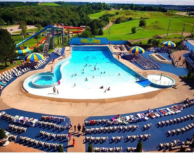 Bird's eye view of people enjoying a large wave pool, surrounded by lounge chairs and two blue and yellow umbrellas