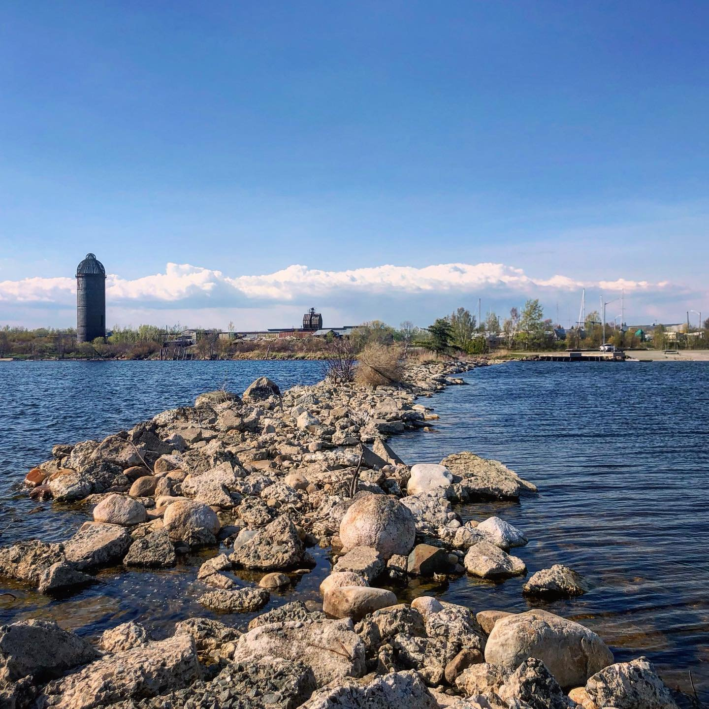 From the perspective of standing on a rocky peninsula surrrounded by water looking at the Marina on shore
