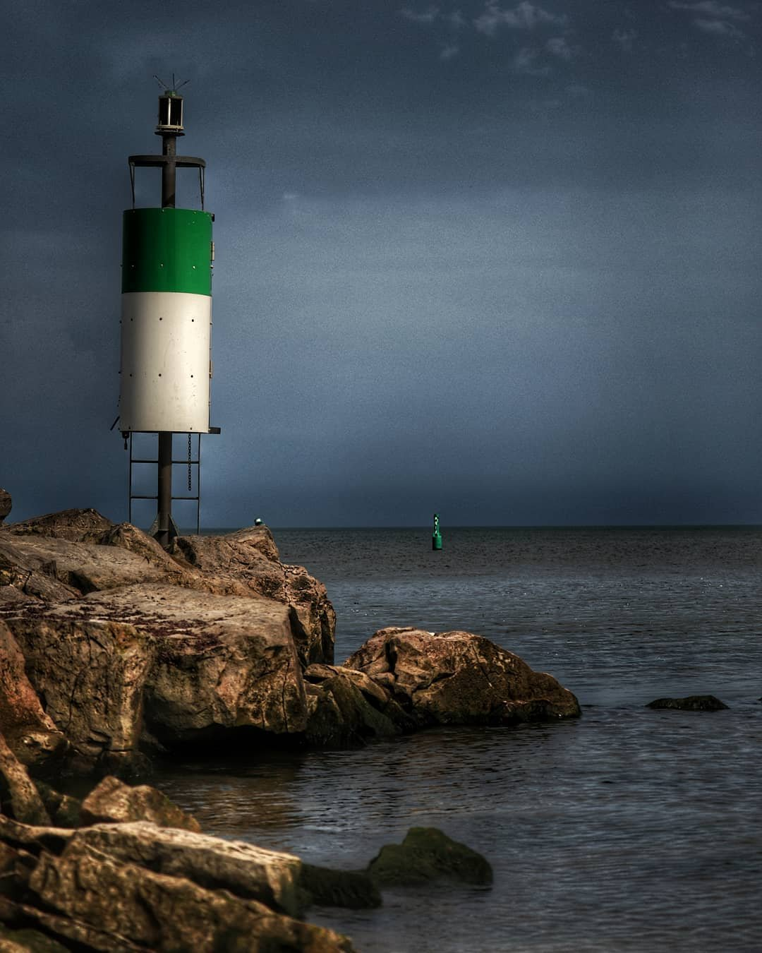A dark sky over the lake with a rocky coastline featuring a warning light system for boats
