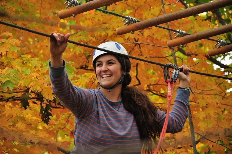 A smiling woman ziplining in a forest