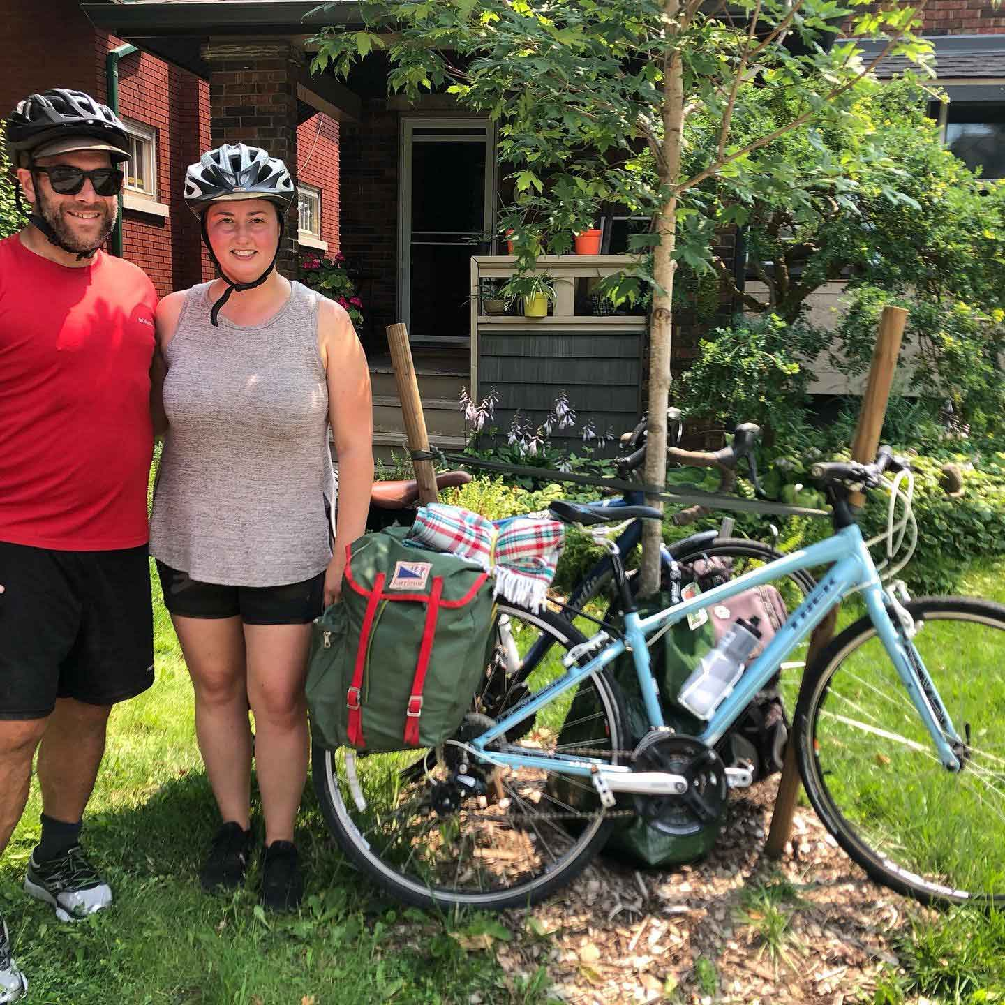 A man and a woman, both wearing bike helmets, pose with a bike that is leaning up against a tree
