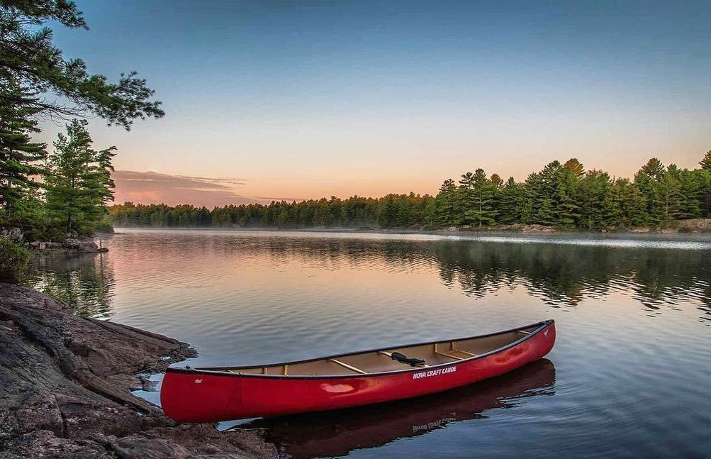 A red canoe partially resting on the shore of a river, as evergreen trees line the river shore with a blue pink sky above
