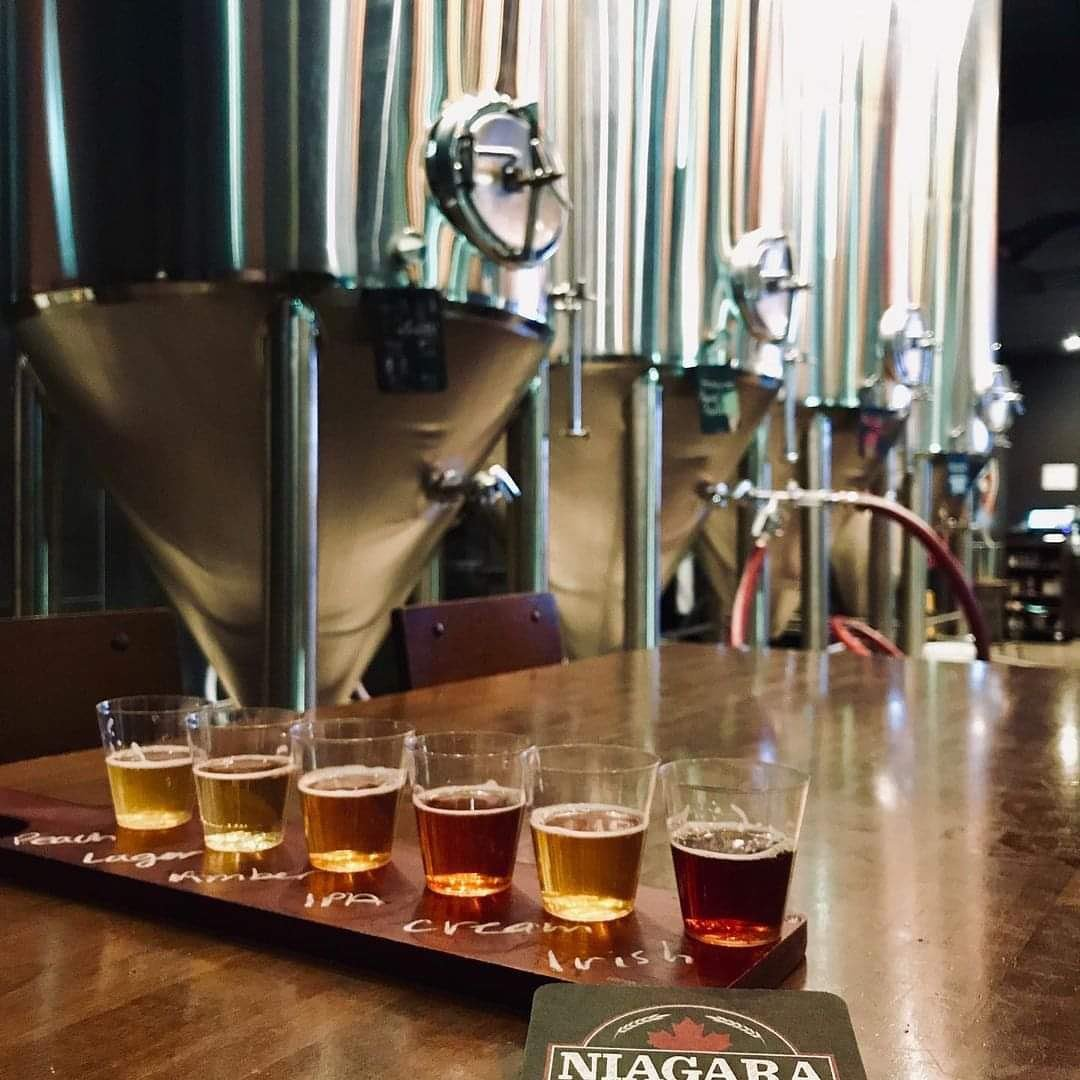 A flight of six sample beers sit on a table in the foreground, as brewing equipment is displayed in the background