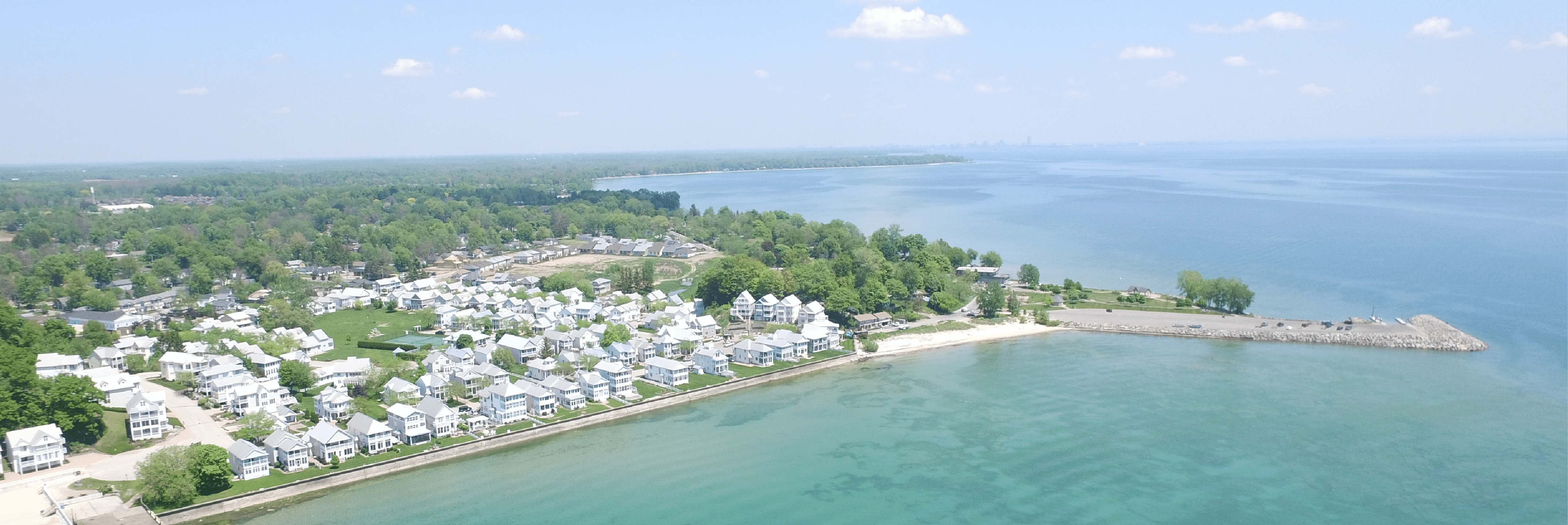 An aerial view of white homes near the lake shore