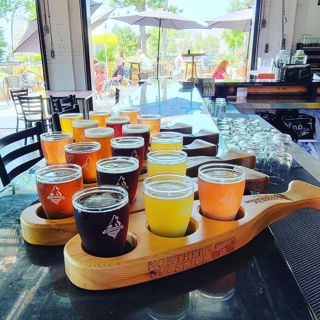 Multiple flights of beer of various colours resting on trays that are whale shaped