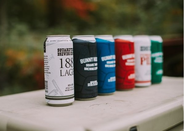 Six different beers cans standing all in a row sitting on a small table