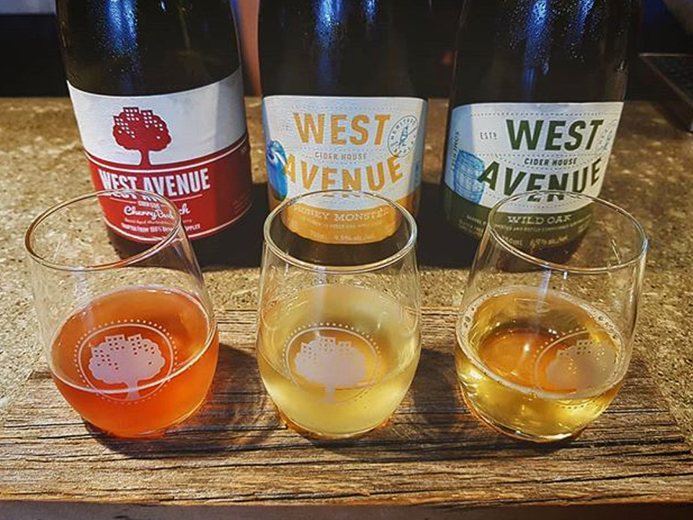 Three bottles of cider lined up behind a tasting flight of three glasses