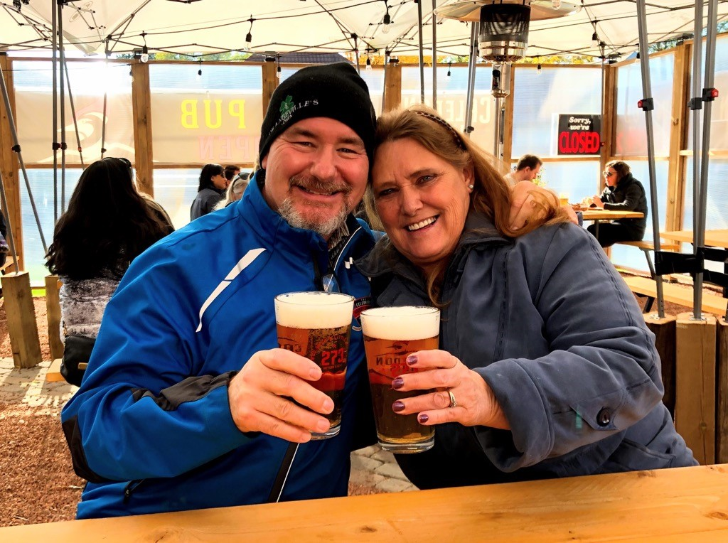 A man and a woman hugging each other drinking beer together