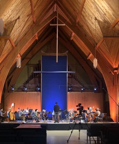 Beautiful wood vaulted ceiling sits above a symphony playing on stage