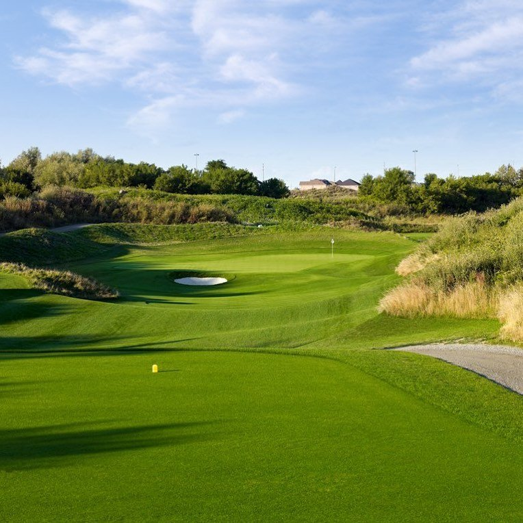 The view of a rolling fairway and green on a golf course