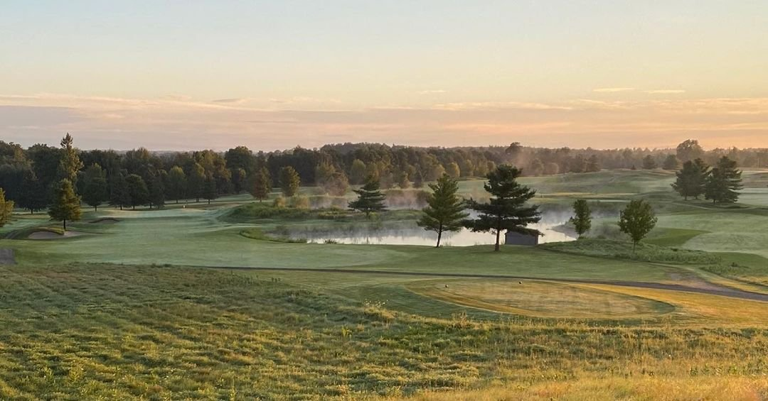 A view of a fairway as mist rises from the pond on a golf course