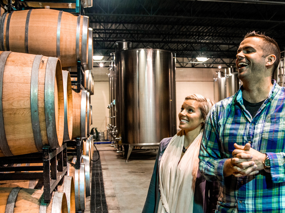 A couple admire a stack of wine barrels in a winery cellar
