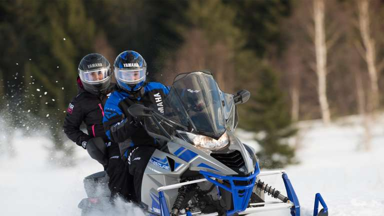 2 people riding a snowmobile