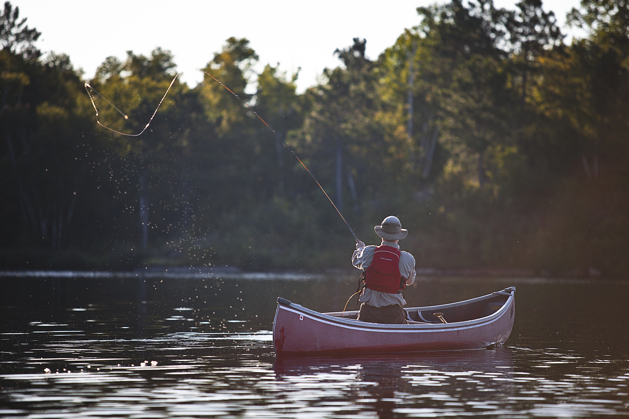 A man casting his line from a boat on a lake