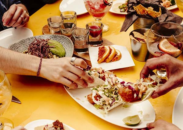 Table pleine de nourriture et de boissons avec des mains d'amis tous atteignant différents plats.