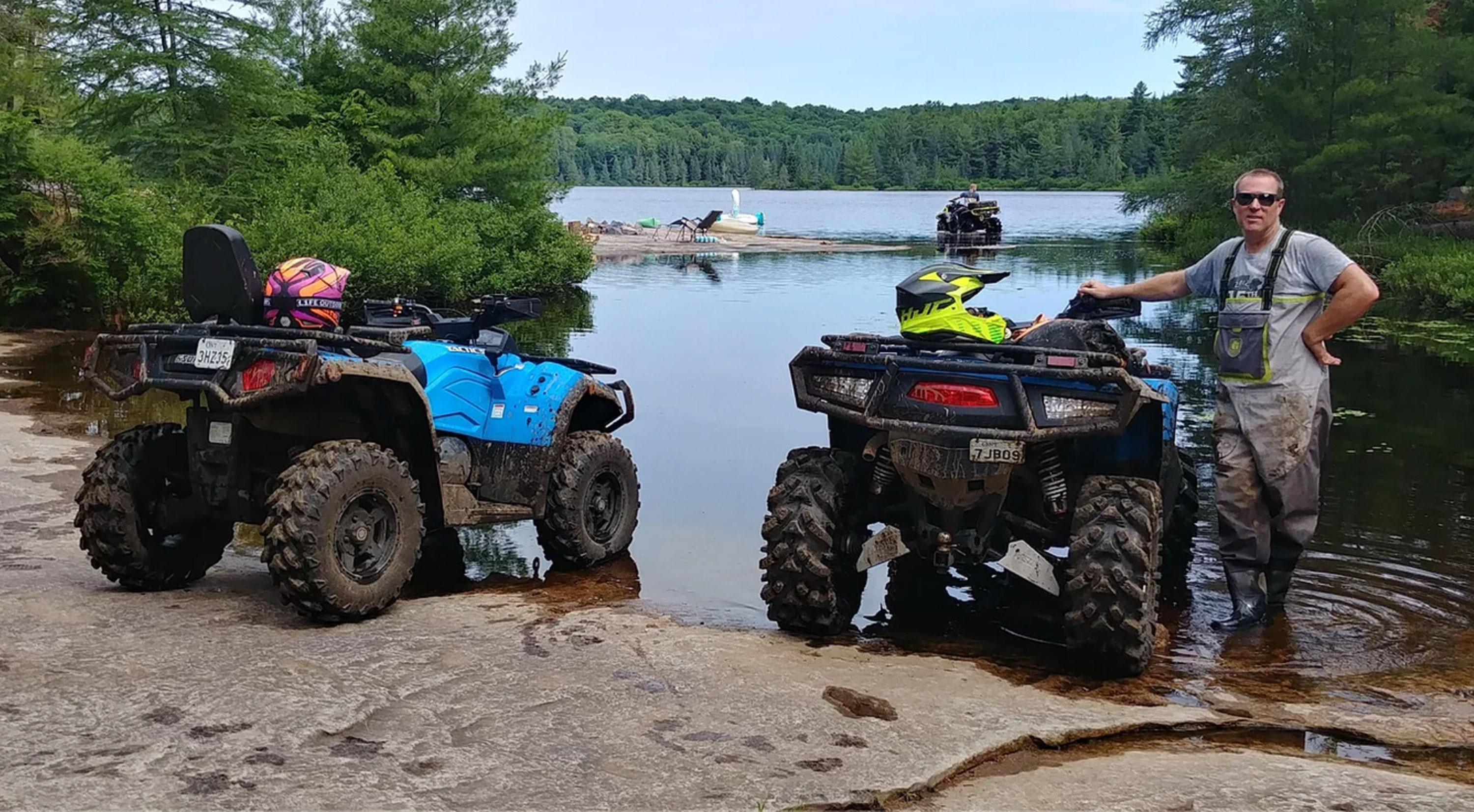 A man poses a long two ATVs on the shore of lake