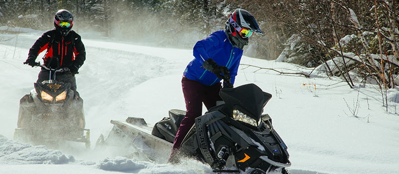 2 snowmobilers ride in the snow