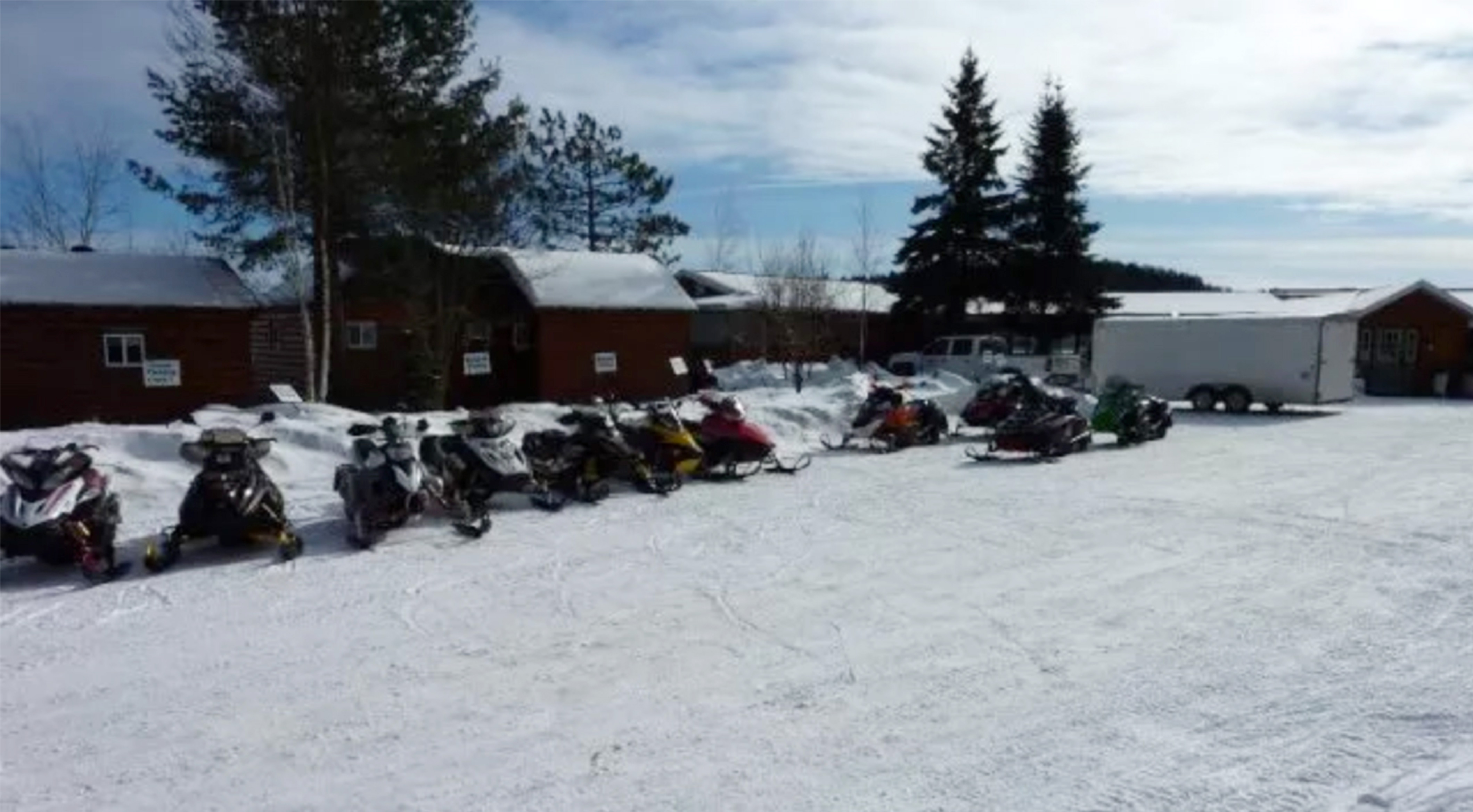 A row of snowmobiles parked in front of buildings