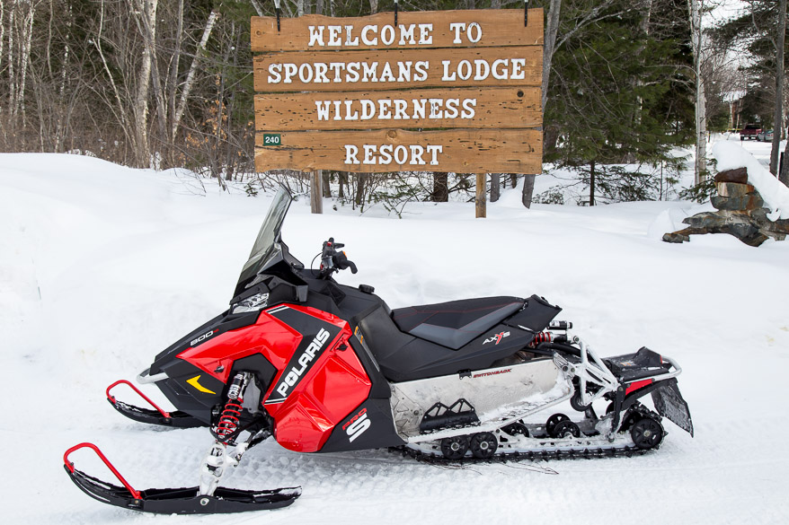 A snowmobile is parked in front of the Sportsman's Lodge sign