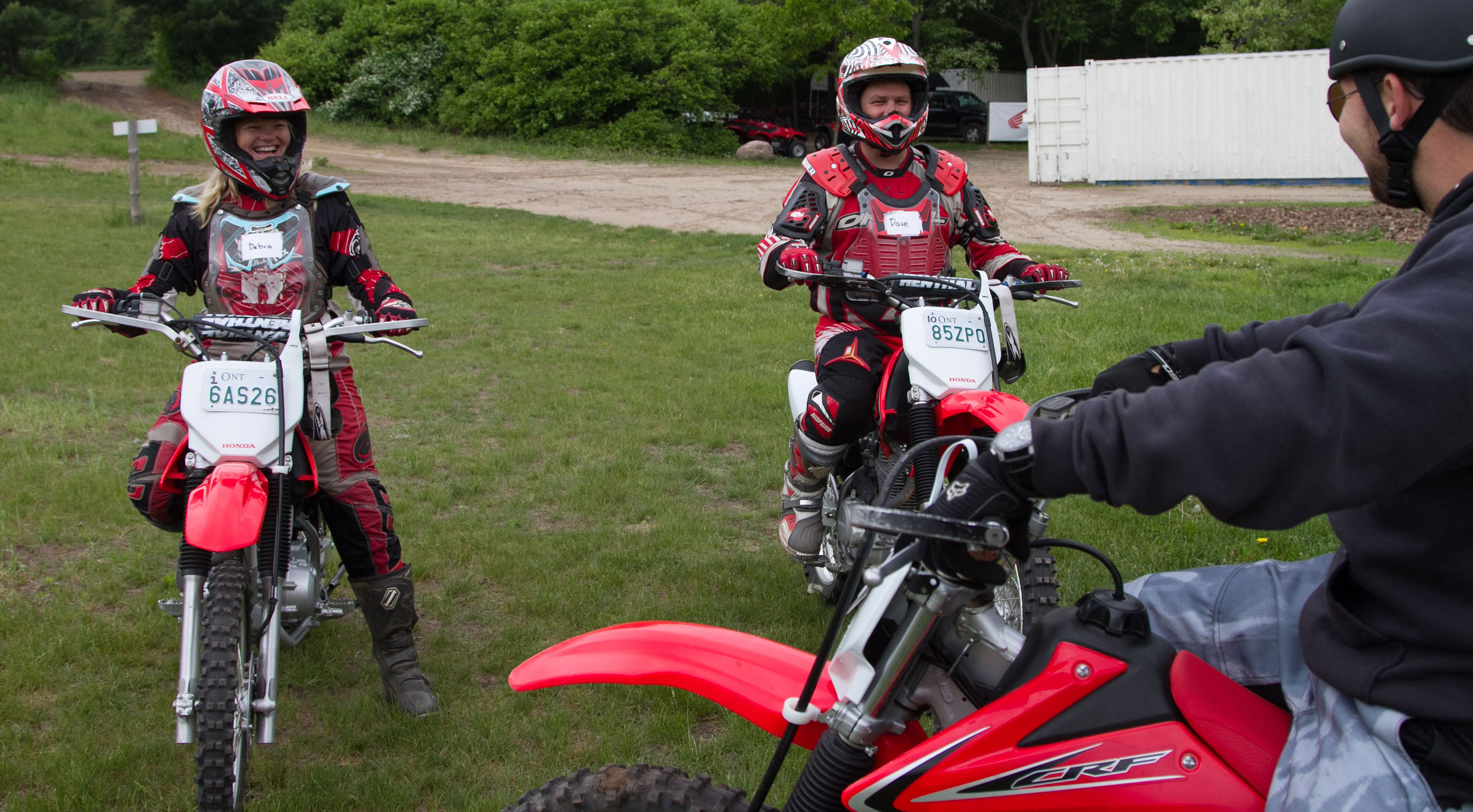 3 people on dirt bikes smiling at each other, getting ready to ride