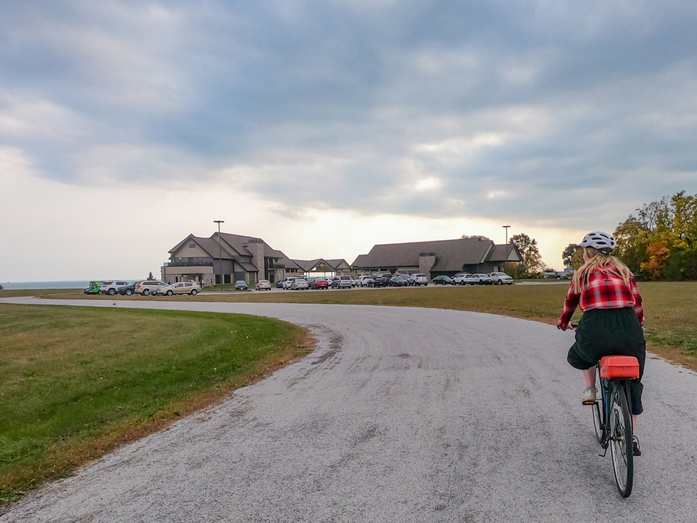 A woman cycles towards an estate winery overlooking the lake