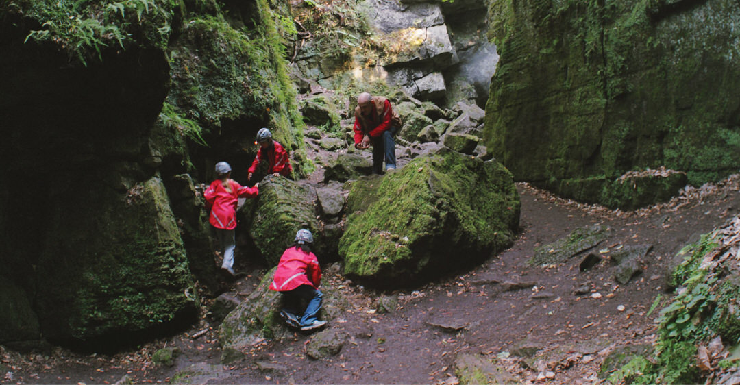 Four people dressed in red jackets are exploring the bottom of a cave
