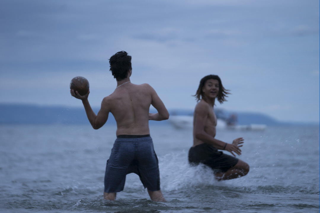 Two men playing football in the water.