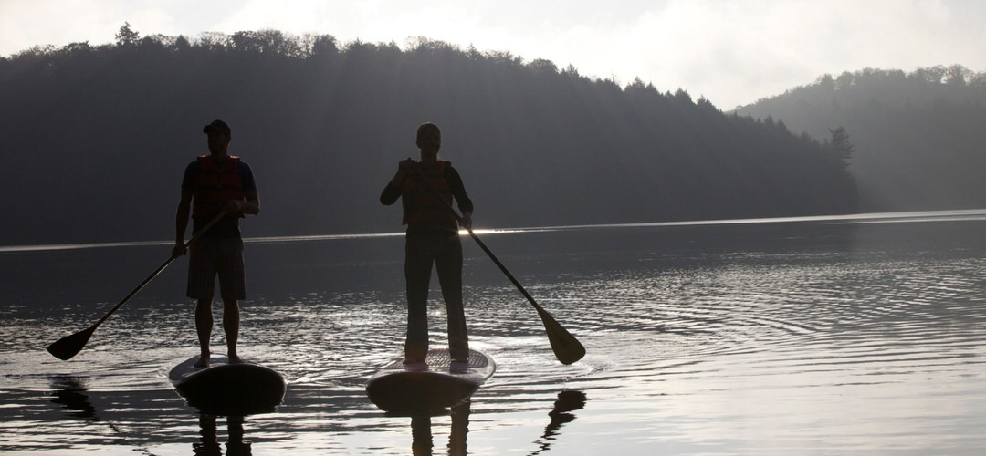 Silhouettes of two men stand up paddling in the water.