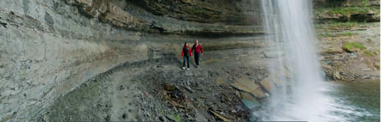 2 people walking behind a waterfall.