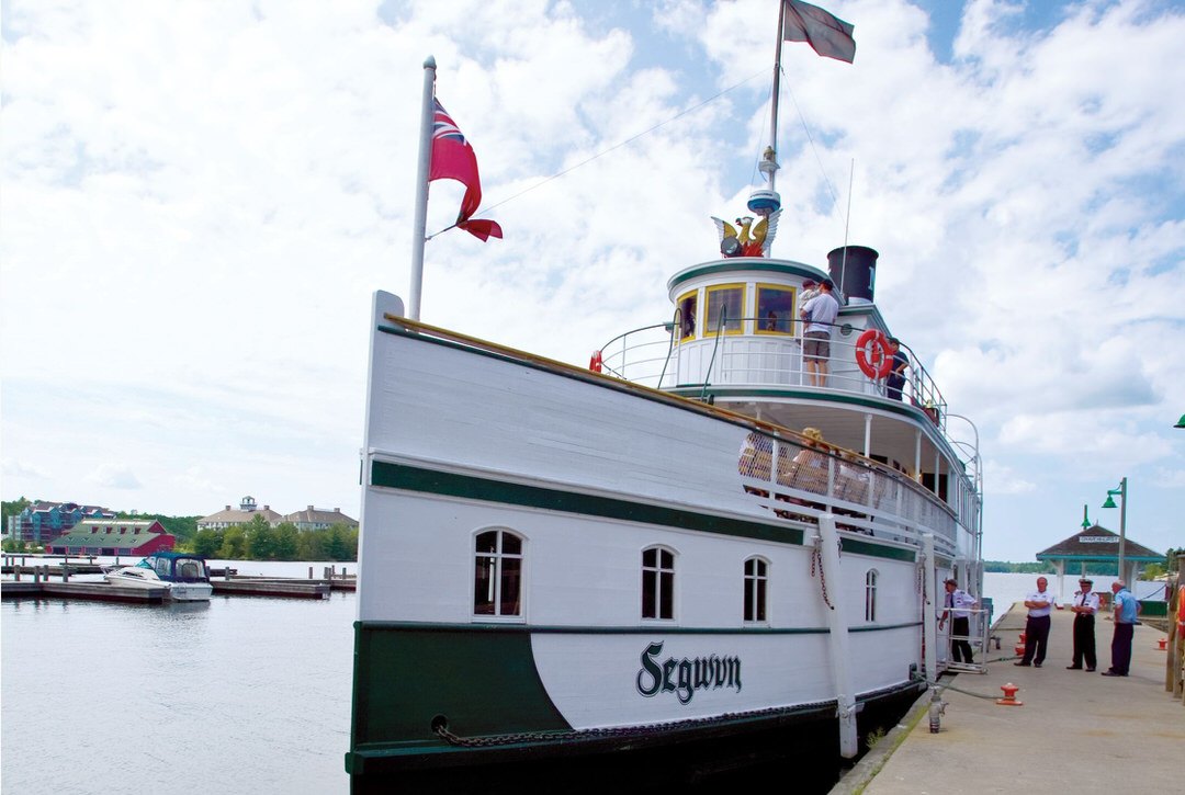 Front view of the Segwun Steamship docked, while the crew is boarding