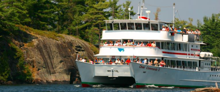 People are on the third deck a ferry viewing the natural landscape.