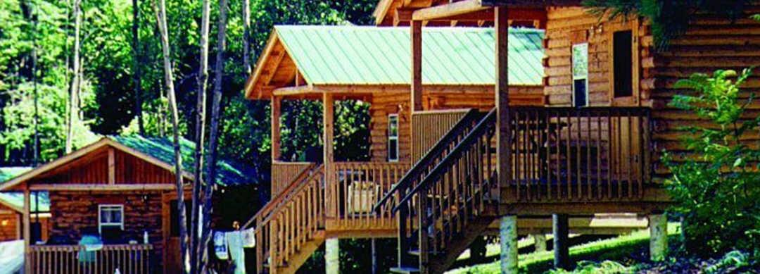 Les cabanes en bois surélevées sont bordées côte à côte, entourées d'arbres