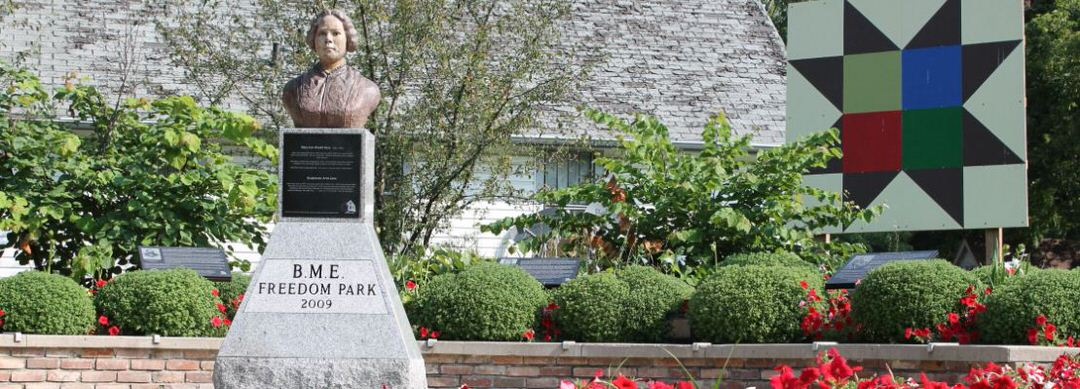 Un buste sur un piédestal, commémorant la liberté ; entouré de jardins et debout est une grande œuvre d'art de forme géométrique