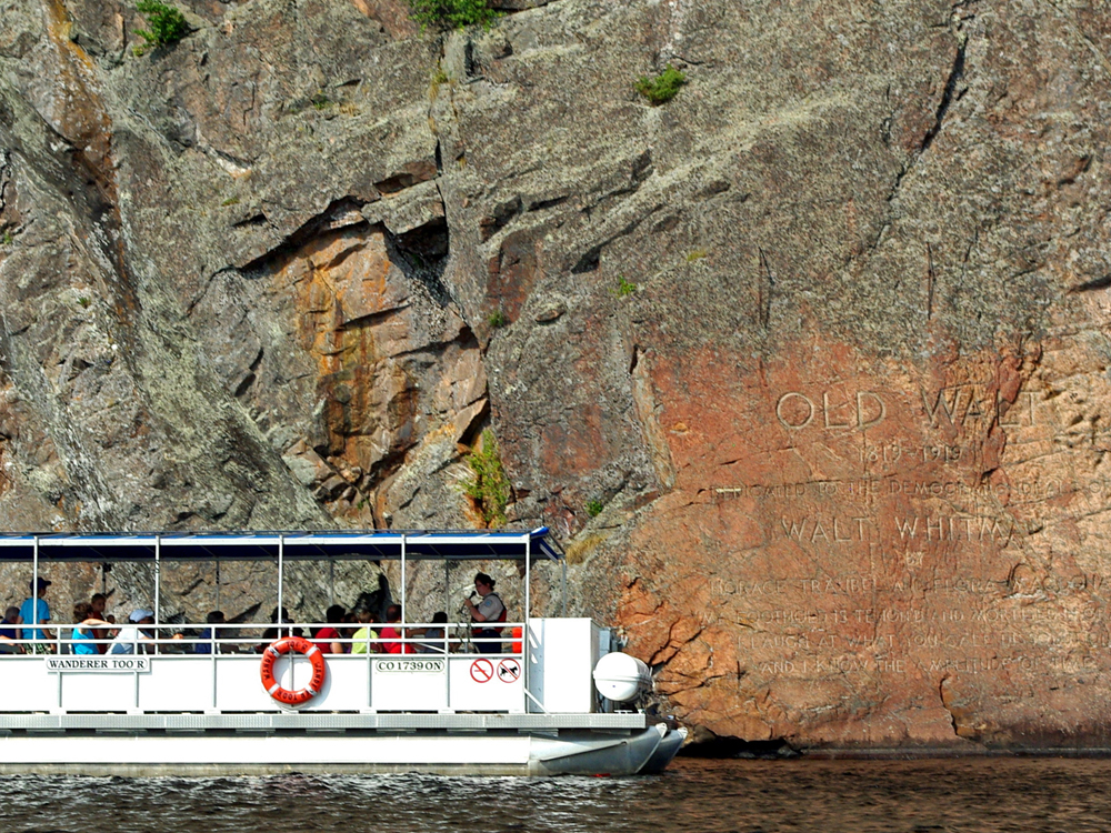 A tour boat cruises past a vast cliff wall