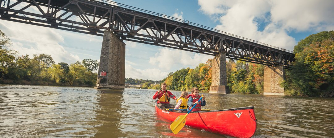 Un homme et deux enfants dans un canoë, ramant en passant sous un pont, avec des arbres de chaque côté de la rivière