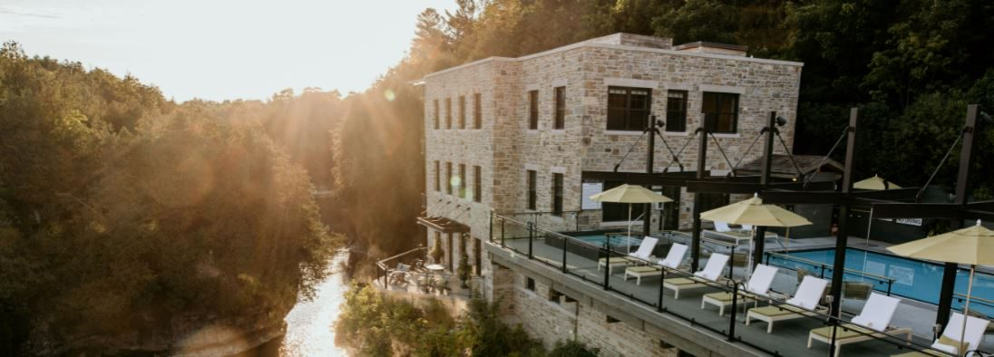 Perched atop the Elora Gorge, a large stone building with a patio full of lounge chairs and umbrellas