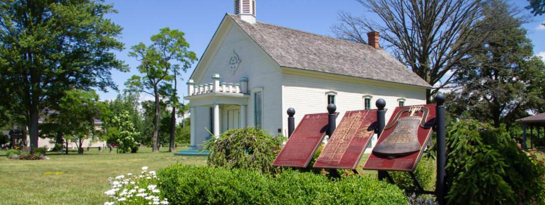Une plaque avec des informations historiques présente le point de repère et la maison entourée d'arbres