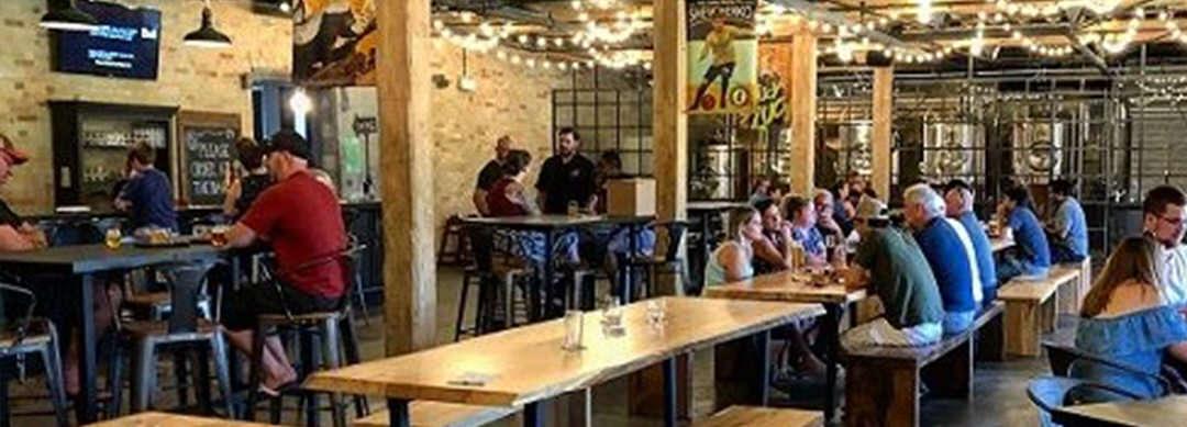 Hommes et femmes assis à des tables, mangeant et buvant dans un pub